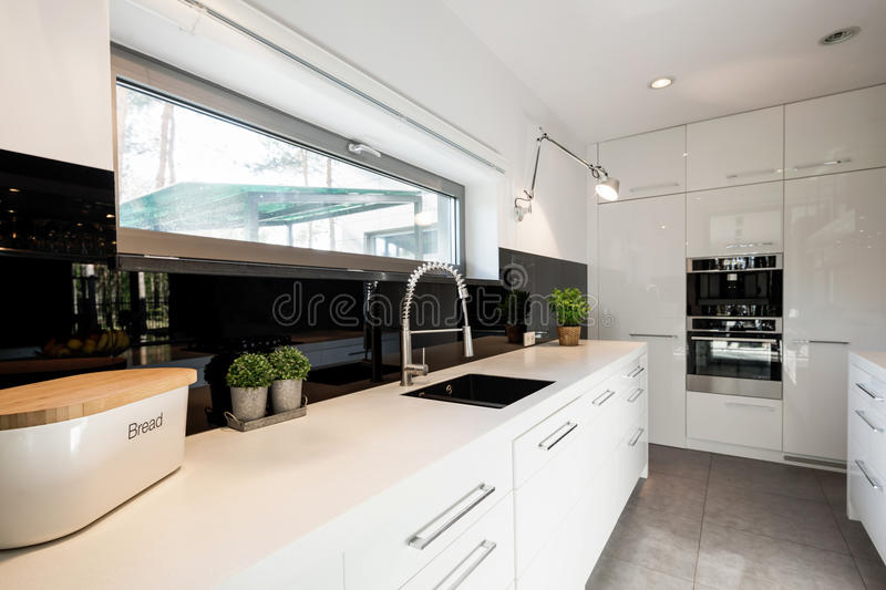 Functional kitchen with white furniture stock photography