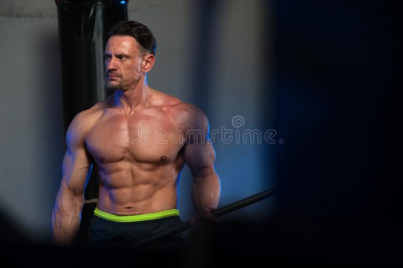 Muscular strong man training with hammer stock photography