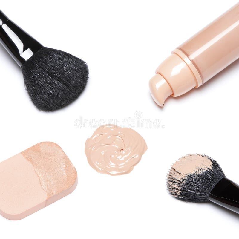 Fundación con los cepillos del maquillaje y la esponja cosmética imagenes de archivo