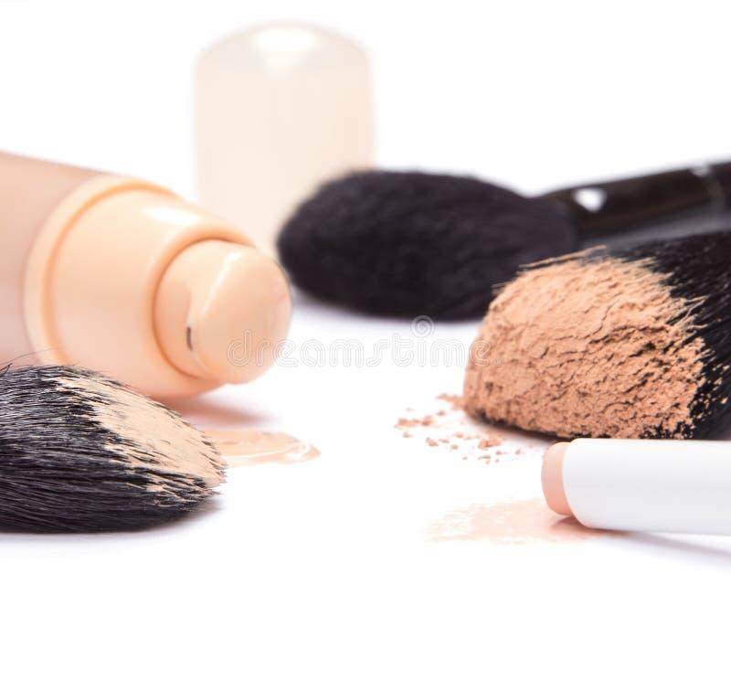 Fundación, lápiz del lápiz corrector y polvo con los cepillos del maquillaje imagen de archivo