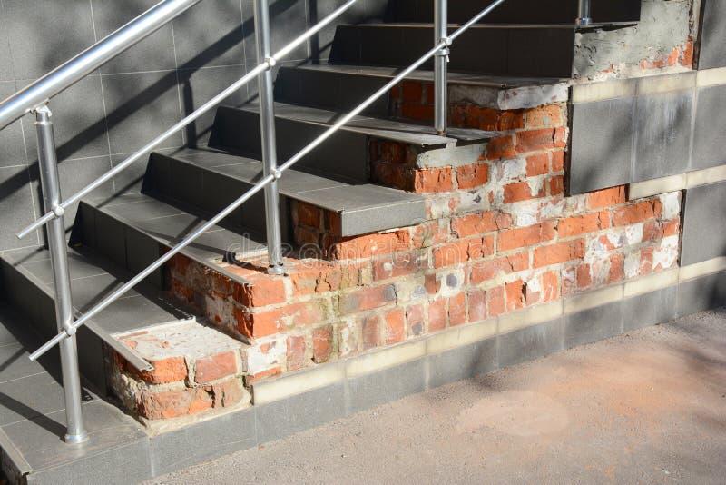 Fundación quebrada de los pasos de la casa con los escapes del agua al aire libre La caja dañada de la escalera necesita reparar imagenes de archivo