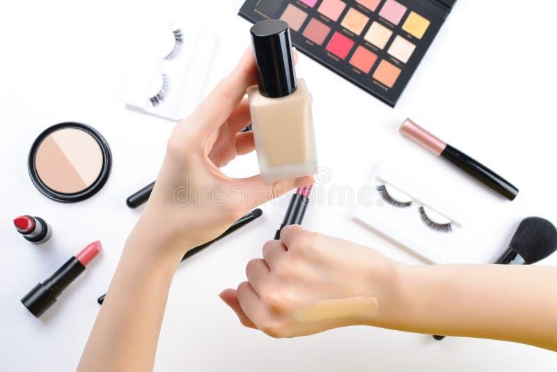 Fundament i kvinnah?nder Yrkesm?ssiga makeupprodukter med kosmetiska sk?nhetsprodukter, fundament, l?ppstift, ?gonskuggor, ?ga arkivbilder