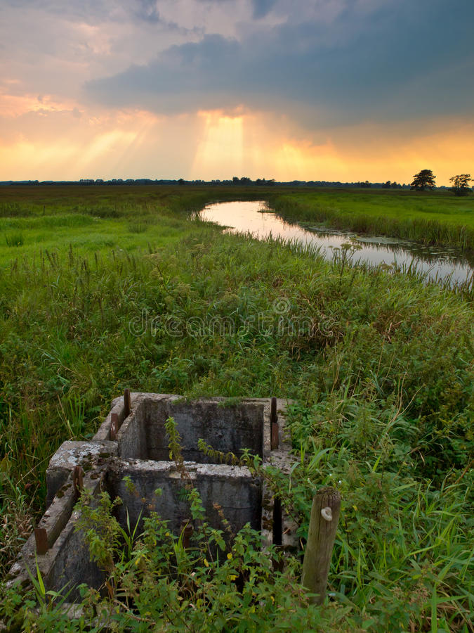 The fundament of a weir. In a nature reserve under a dramatic sky stock photo