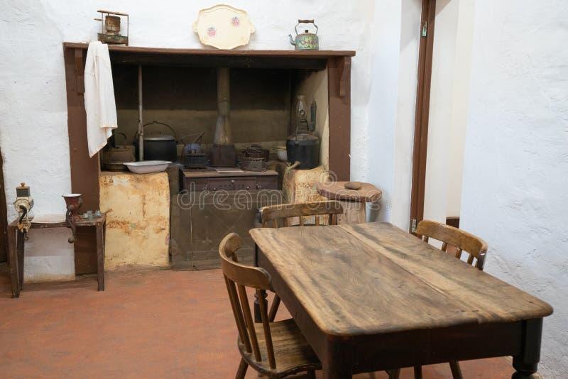 Fundamentele oude uitstekende keuken met rustieke houten lijst houten-brander en witte muren stock afbeelding