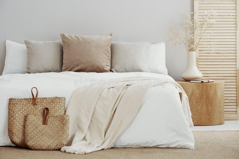 Fundamento branco e bege na cama de casal no interior simples foto de stock