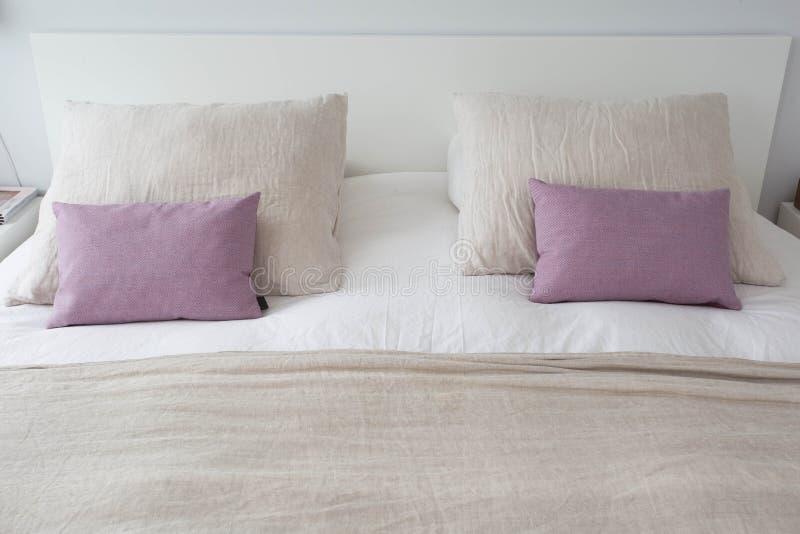 Fundamento composto no quarto confortável moderno com o bedsheet branco limpo e no descanso com a cama acolhedor clara, limpa e c fotografia de stock