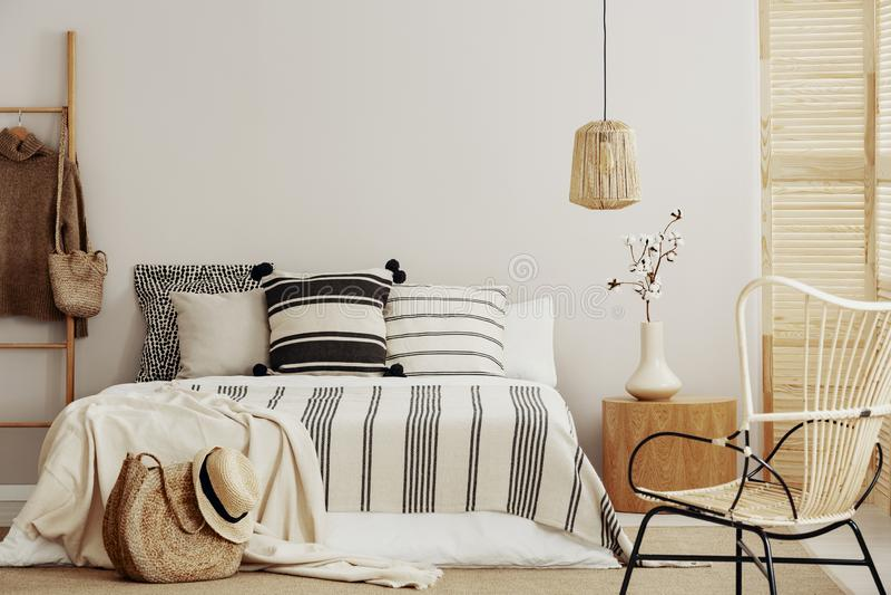 Fundamento listrado na cama enorme no quarto contemporâneo interior com espaço da cadeira de vime e da cópia na parede vazia foto de stock