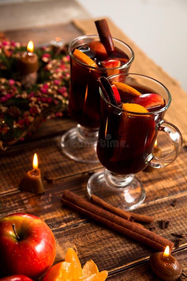 Funderad near stearinljus för vin med frukter och kryddor på trätabellen Jul Vintervärmedrink med receptingredienser omkring Tw fotografering för bildbyråer