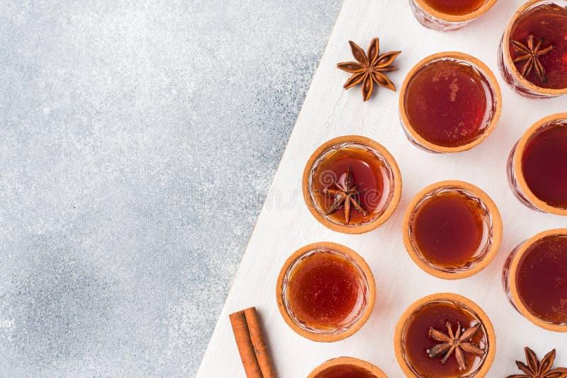 Funderad vinäppeljuice i små buntar med kanel och anis Begreppet av coctailstången Kopieringsutrymme för bästa sikt arkivbilder
