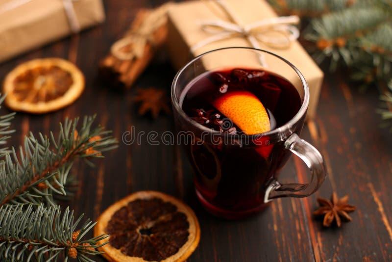 Funderade vin, gåva och kryddor på tabellen bredvid trädet Begreppet av jul och det nya året, dekor royaltyfri fotografi