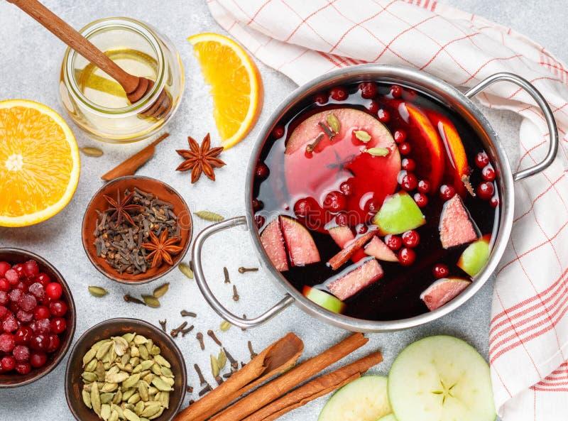 Funderat vin är en traditionell vinterdrink med rött vin, honung, apelsinen, gröna Apple, tranbäret och kryddor royaltyfri fotografi