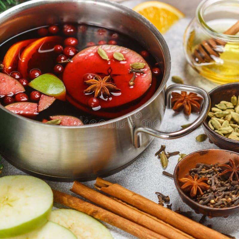 Funderat vin är en traditionell vinterdrink med rött vin, honung, apelsinen, gröna Apple, tranbäret och kryddor royaltyfria foton