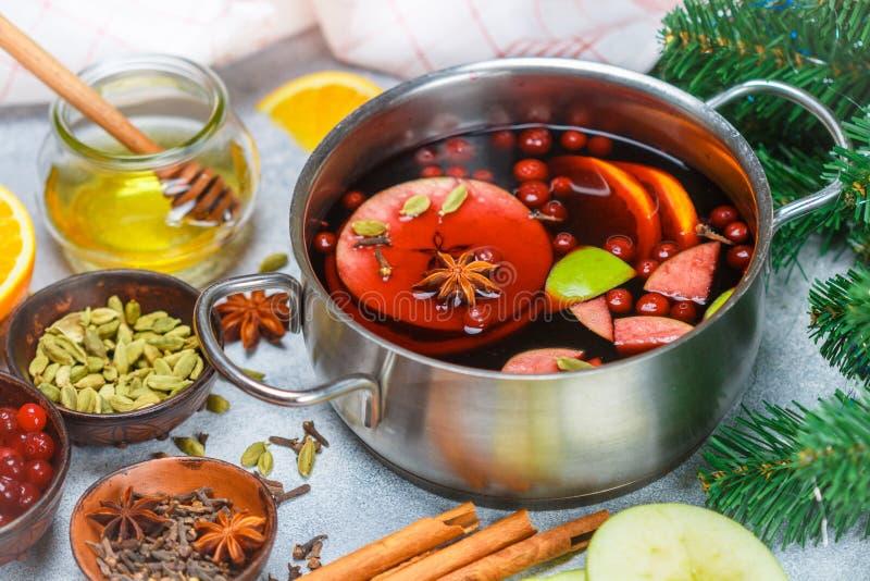 Funderat vin är en traditionell vinterdrink med rött vin, honung, apelsinen, gröna Apple, tranbäret och kryddor royaltyfri foto