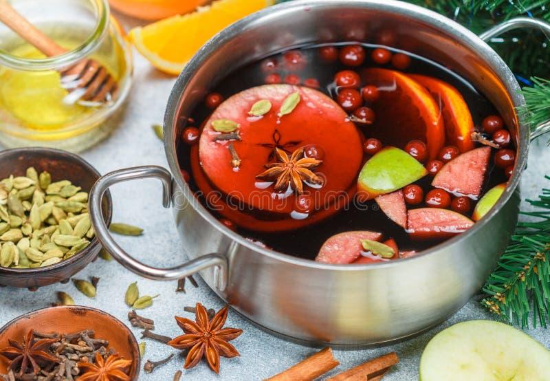 Funderat vin är en traditionell vinterdrink med rött vin, honung, apelsinen, gröna Apple, tranbäret och kryddor royaltyfri bild