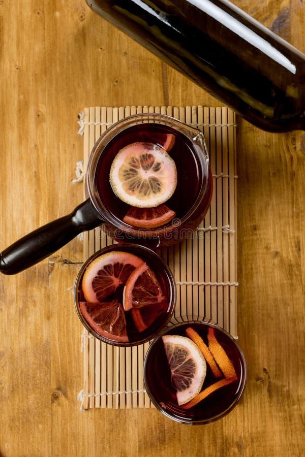 Funderat vin i exponeringsglas med flaskan på träbakgrund, bästa sikt arkivbilder