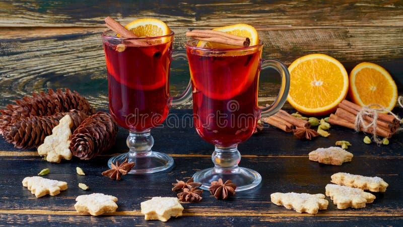 Funderat vin i exponeringsglasen med olika vinterkryddor på den svarta träbakgrunden dekorerade med julkakor arkivbilder