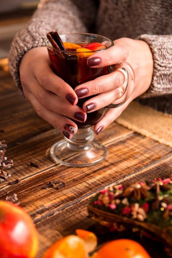 Funderat vin i kvinnlig räcker, kryddor och fruktingredienser på trätabellen Vintervärmedrink Jul royaltyfria foton