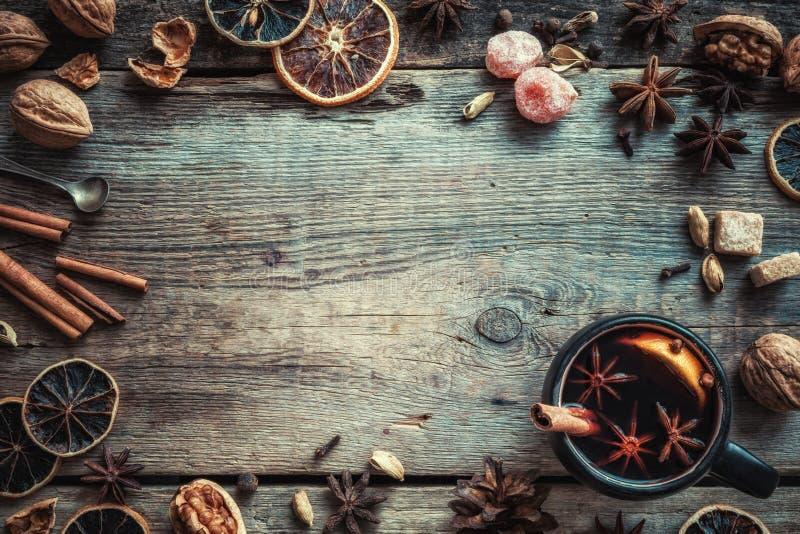 Funderat vin i lantligt rånar med kryddor och ingredienser på tabellen royaltyfri bild