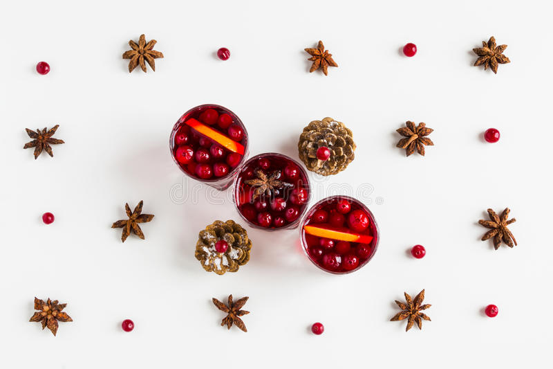 Funderat vin i små exponeringsglas med tranbär, anis och apelsiner Vit bakgrund, bästa sikt arkivfoton