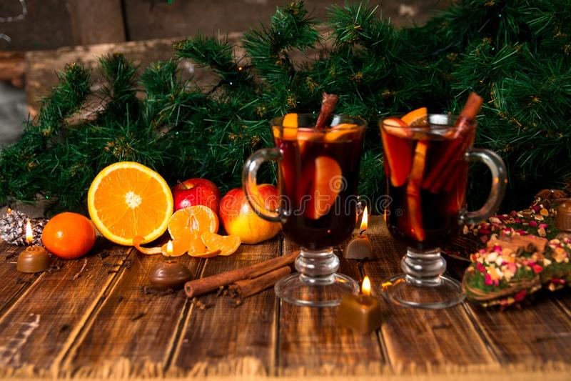 Funderat vin med frukter och kryddor på trätabellen Julpynt i bakgrund exponeringsglas två Vintervärmedrink med beträffande arkivbild