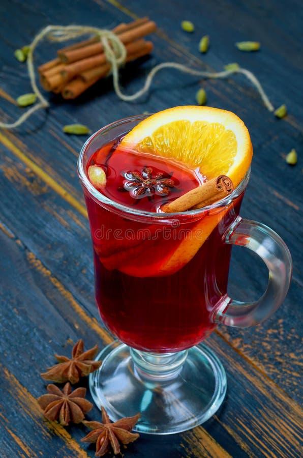 Funderat vin med orange skiva- och vinterkryddor - kanel-, kardemumma- och anisstjärnor på den svarta träbakgrunden royaltyfri bild