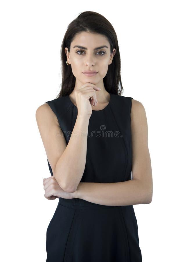 Fundersam affärskvinna med ett finger under hakan arkivfoto