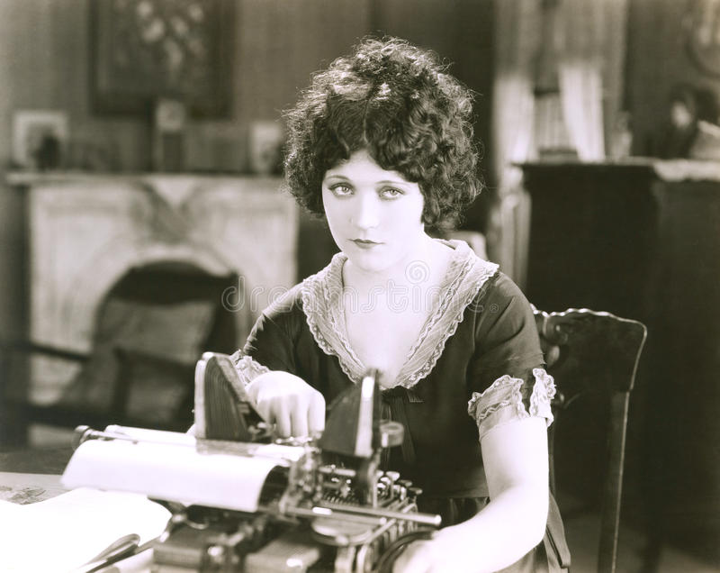 Fundersam affärskvinna med skrivmaskinen på skrivbordet i regeringsställning fotografering för bildbyråer