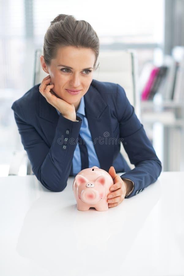 Fundersam affärskvinna med spargrisen royaltyfri fotografi