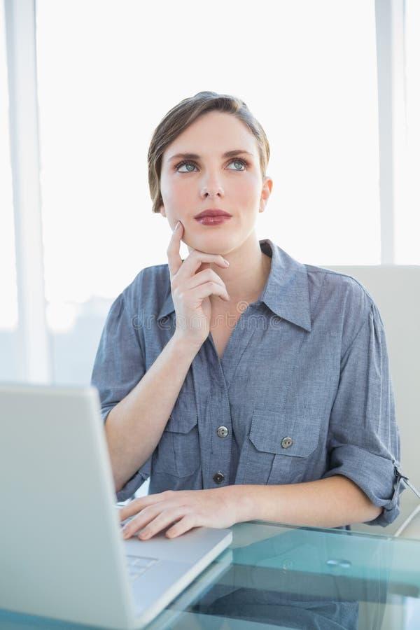 Fundersam affärskvinna som använder hennes anteckningsbok, medan sitta på hennes skrivbord royaltyfria bilder