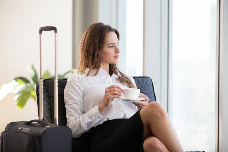Fundersam affärskvinna som dricker kaffe med bagage i flygplats arkivfoto