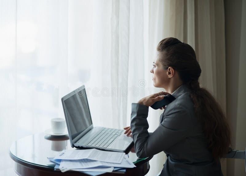 Fundersam affärskvinna som fungerar på hotellrum royaltyfria foton