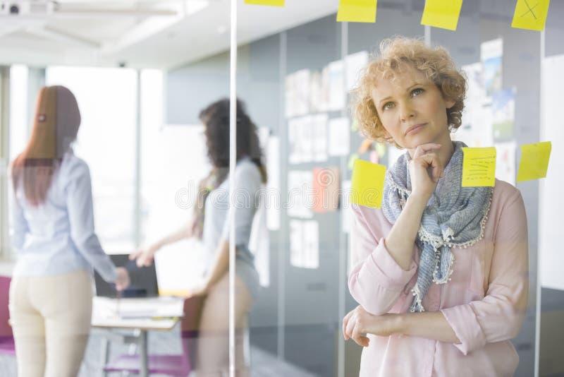Fundersam affärskvinna som läser klibbiga anmärkningar på exponeringsglas med kollegor i bakgrund fotografering för bildbyråer