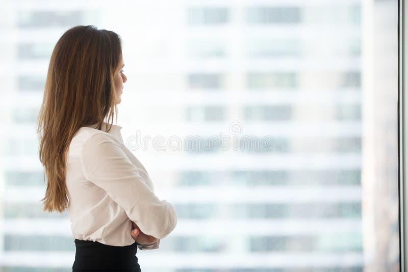 Fundersam affärskvinna som långt borta ser tänka av framgång arkivbild