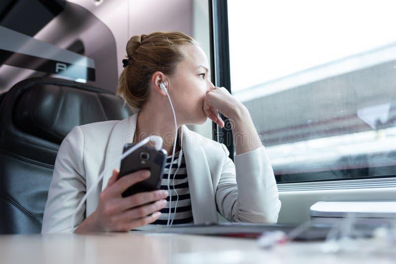 Fundersam affärskvinna som lyssnar till podcasten på mobiltelefonen, medan resa med drevet royaltyfri fotografi
