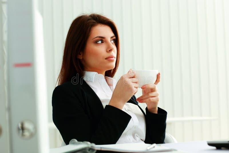 Fundersam affärskvinnainnehavkopp och se upp royaltyfria foton