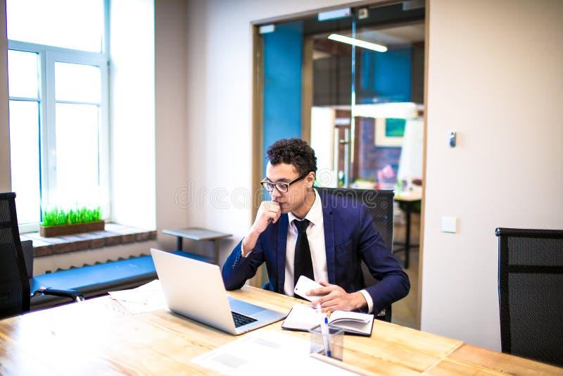 Fundersam affärsman i hållande ögonen på presentation för dräkt på bärbar datordatoren som i regeringsställning sitter inre arkivbild