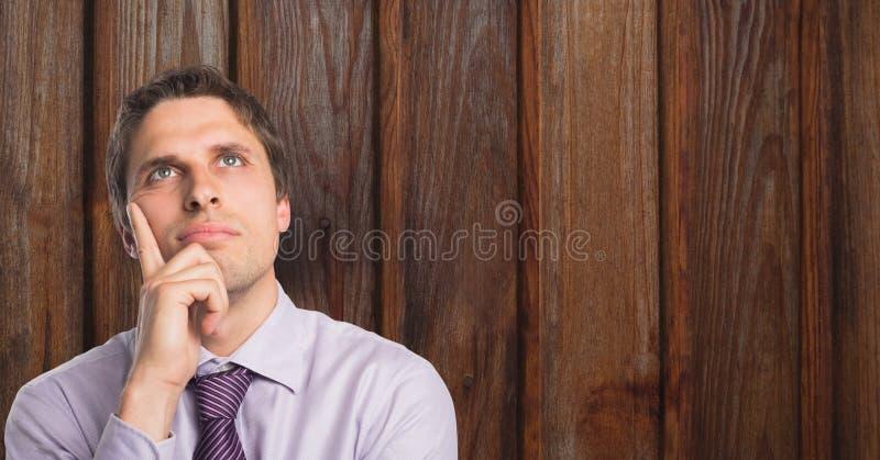 Fundersam affärsman med handen på hakan mot trä royaltyfria foton