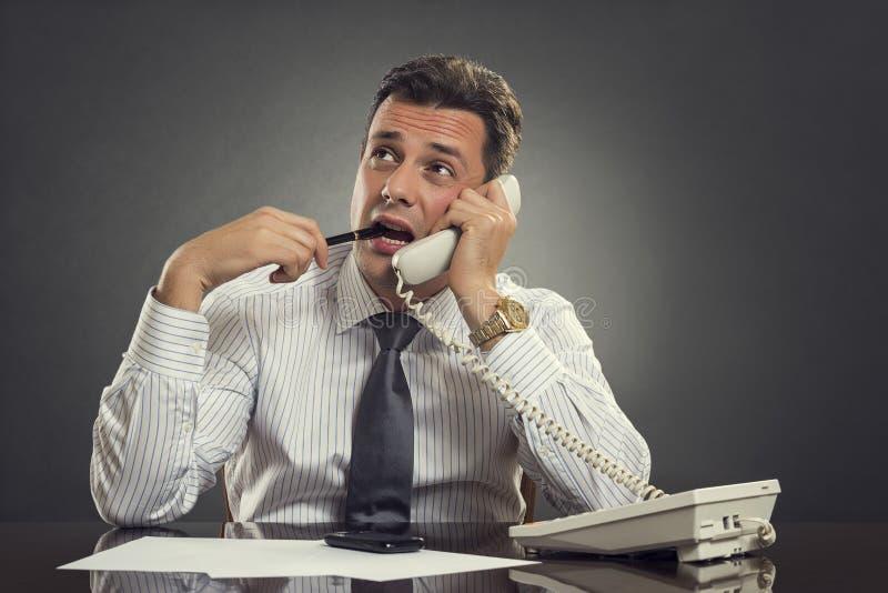 Fundersam affärsman på telefonen arkivfoto