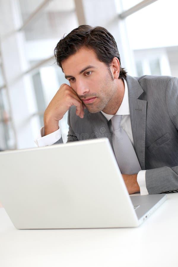 Fundersam affärsman som arbetar på bärbara datorn arkivfoton