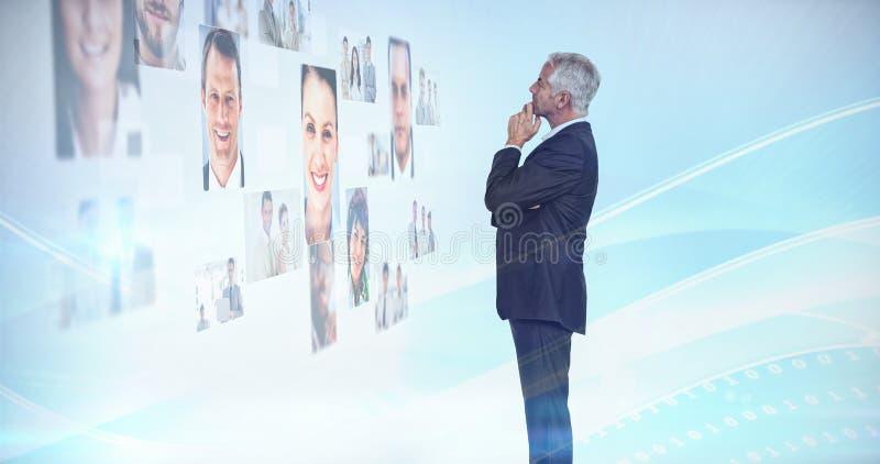 Fundersam affärsman som ser en vägg som täckas av profilbilder royaltyfria foton