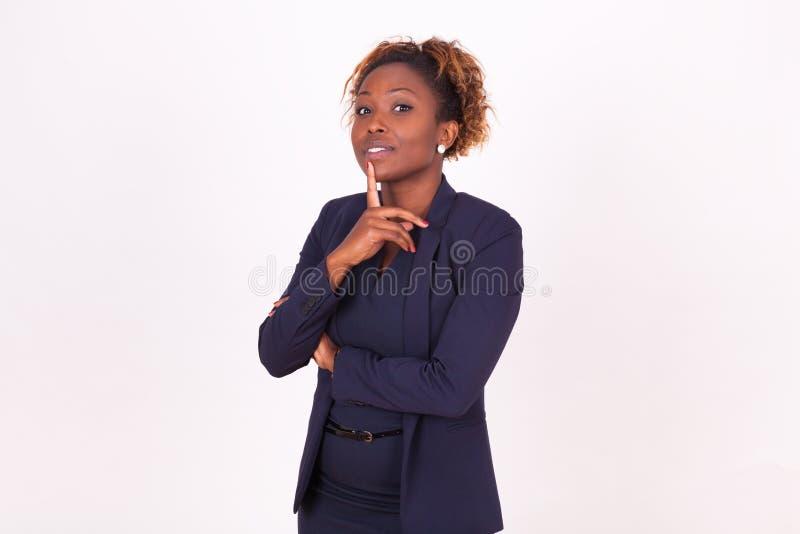 Fundersam afrikansk amerikanaffärskvinna med, isolerat på wh fotografering för bildbyråer