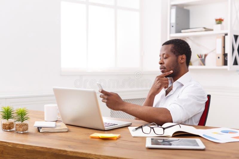 Fundersam afrikansk amerikanaffärsman som smsar på telefonen, medan arbeta på bärbara datorn arkivfoton