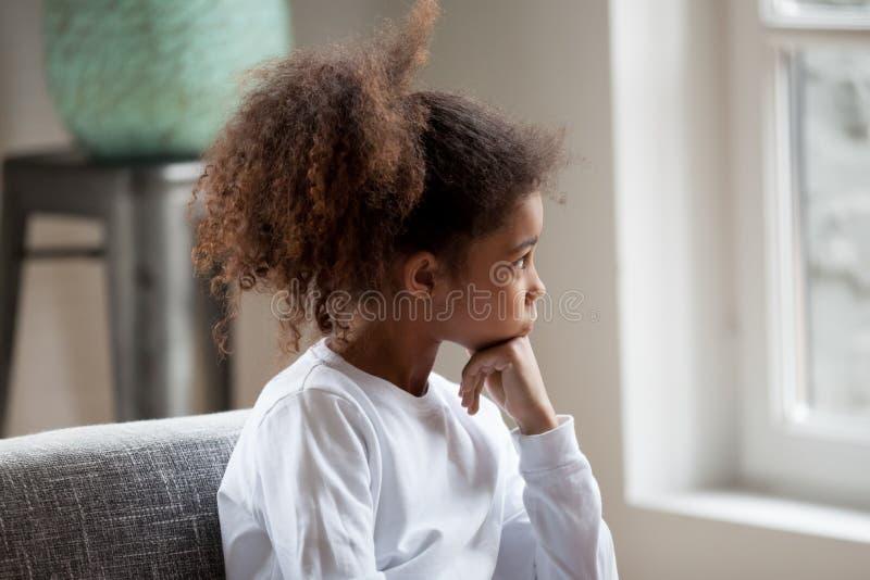 Fundersam afrikansk amerikanförskolebarnflicka som ser i fönster royaltyfria bilder
