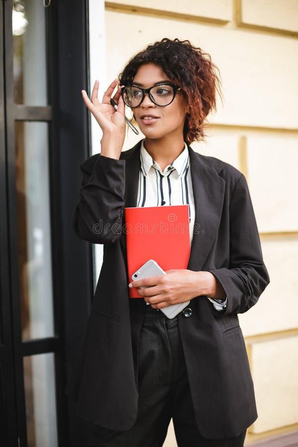 Fundersam afrikansk amerikanflicka i exponeringsglas som in står och dreamily åt sidan ser med mobiltelefonen i hand nätt lady fotografering för bildbyråer