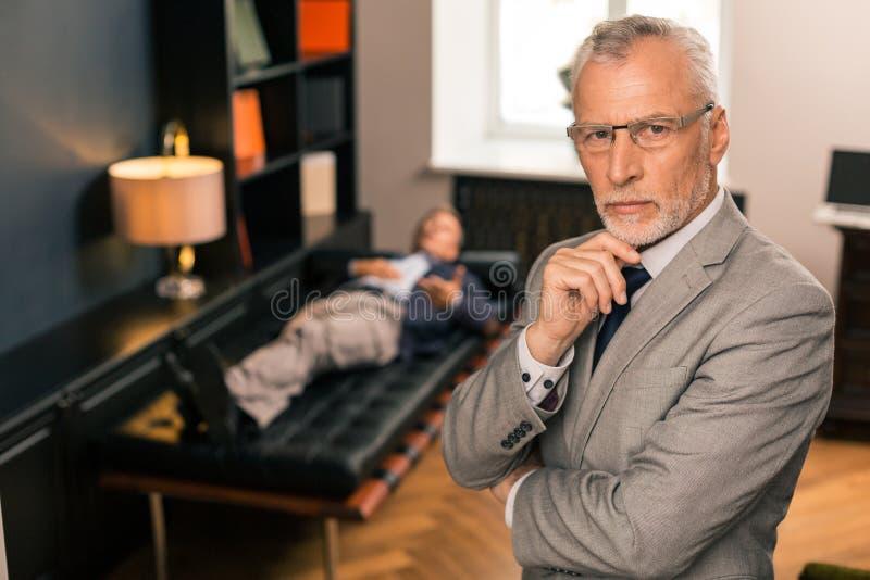 Fundersam allvarlig doktor som står bredvid hans patient arkivbild