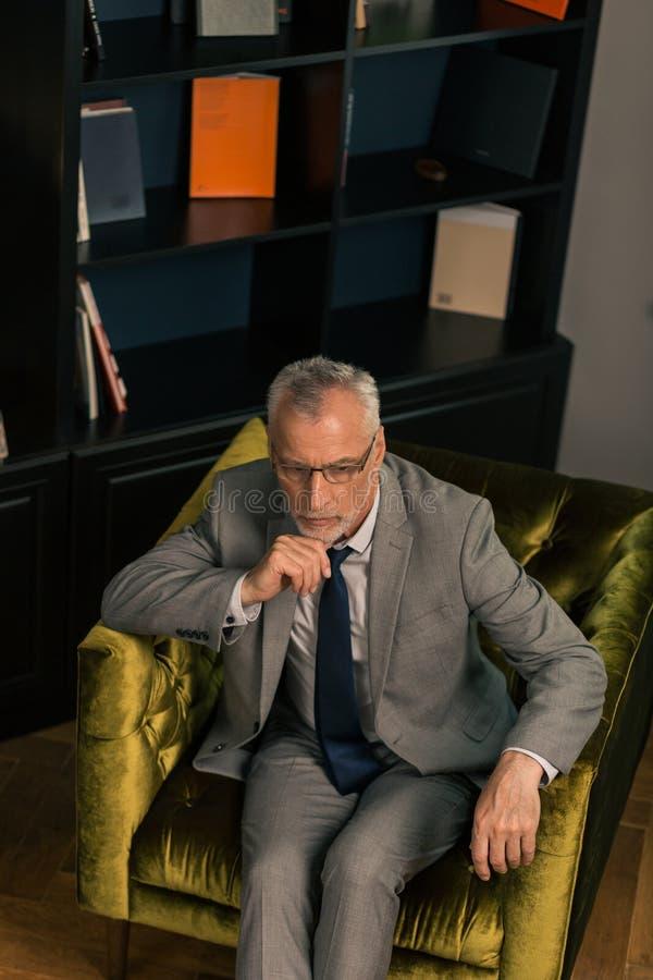 Fundersam allvarlig grå färg-haired man som sitter i en fåtölj arkivfoton