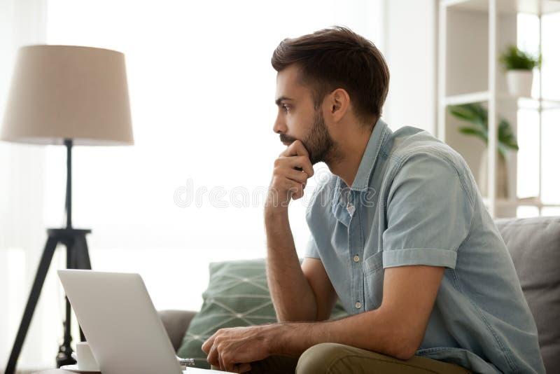 Fundersam allvarlig man som hemma sitter med bärbara datorn och att göra beslut royaltyfria foton