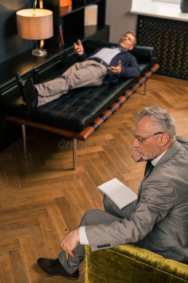 Fundersam allvarlig psykoterapeut som sitter bredvid hans patient fotografering för bildbyråer