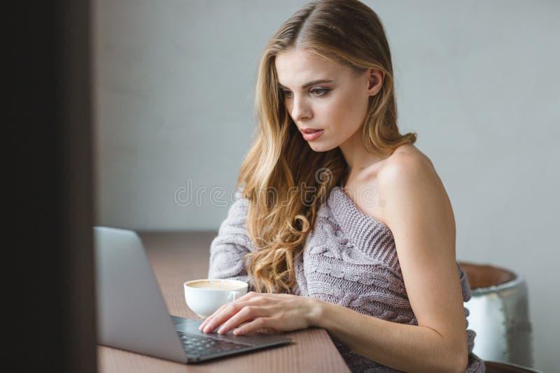 Fundersam attraktiv flicka som dricker kaffe och använder bärbara datorn royaltyfri bild