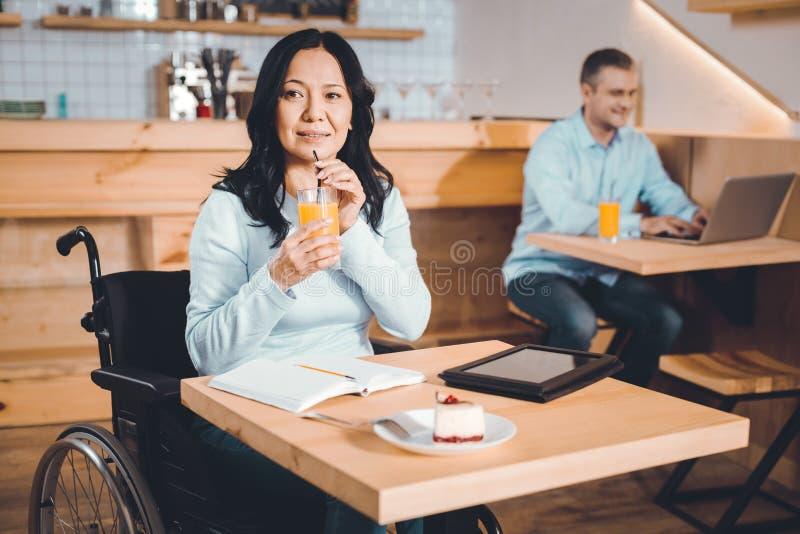 Fundersam dam som dricker fruktsaft i ett kafé royaltyfri fotografi
